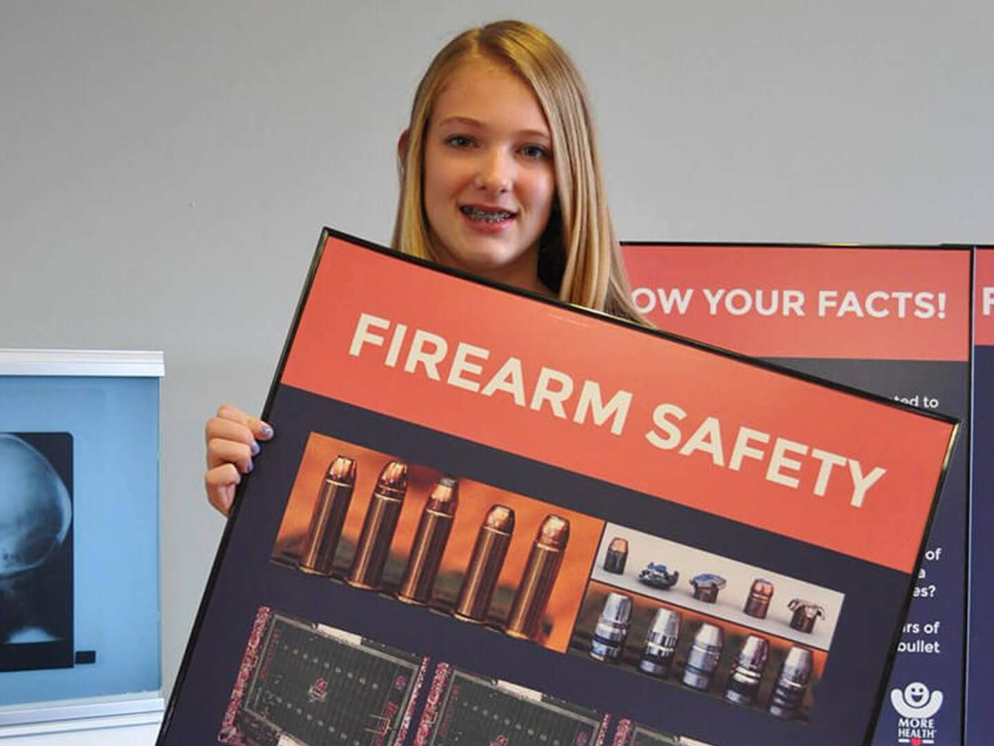teenager holding a More Health Firearm Safety Poster. In the background is an x-ray of a skull.